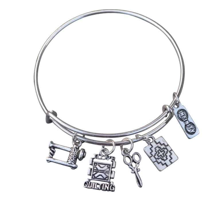 A picture of a bracelet with sewing and quilting charms on it