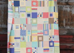 A quilt made of different sizes of squares and strips